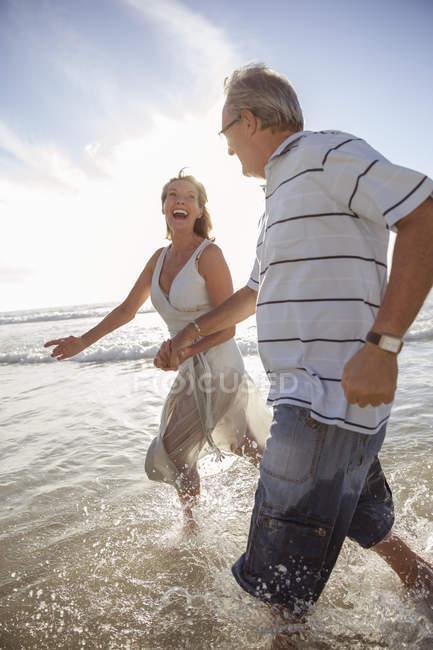 Пари дорослих, які грають у хвилі на пляжі — стокове фото