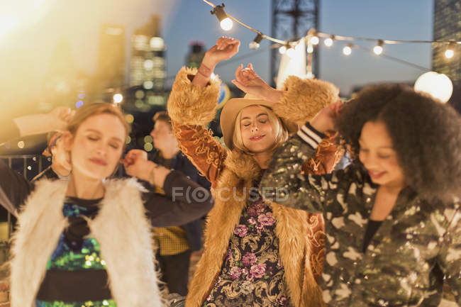 Young adult women dancing at nighttime rooftop party — Stockfoto