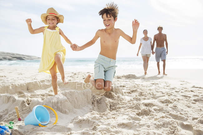 Children kicking down sandcastle on beach — Stock Photo