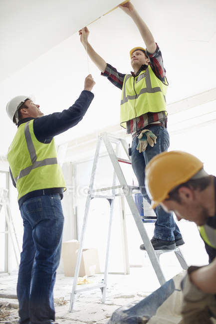 Construction worker on ladder at construction site — Stock Photo