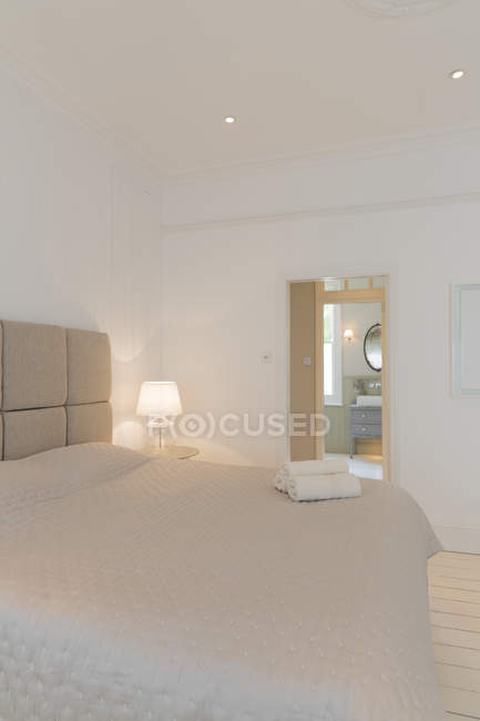 Bed and towels in modern bedroom — Stock Photo