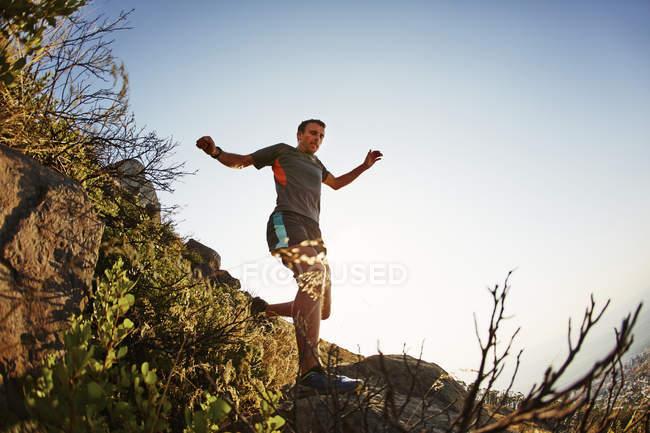 Male runner jumping and descending trail — Stockfoto