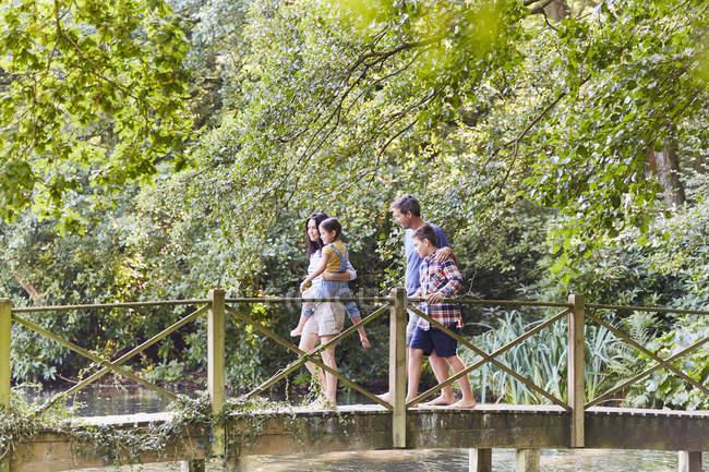 Puente peatonal cruce familiar en parque con árboles - foto de stock