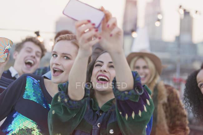 Junge Frauen lachen und nehmen Selfie auf Party auf dem Dach — Stockfoto