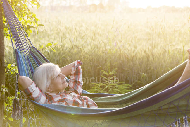Serene senior woman laying in hammock next to rural wheat field — Stock Photo