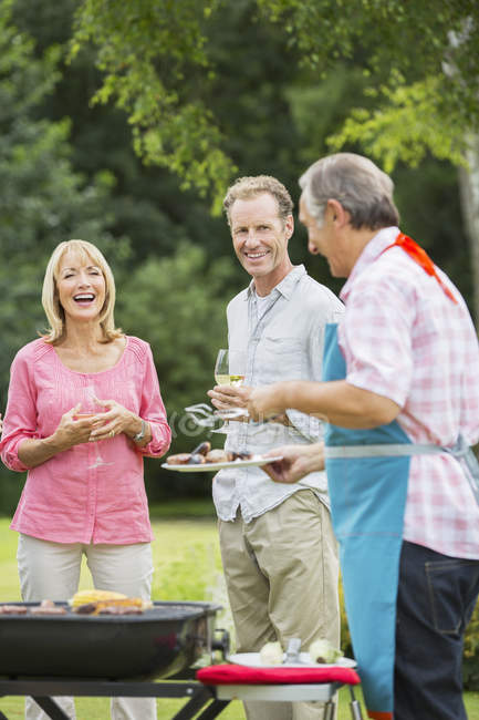 Happy family standing at barbecue in backyard — Stock Photo