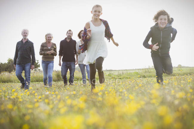 Energetic brother and sister running in meadow with family in background — Stock Photo
