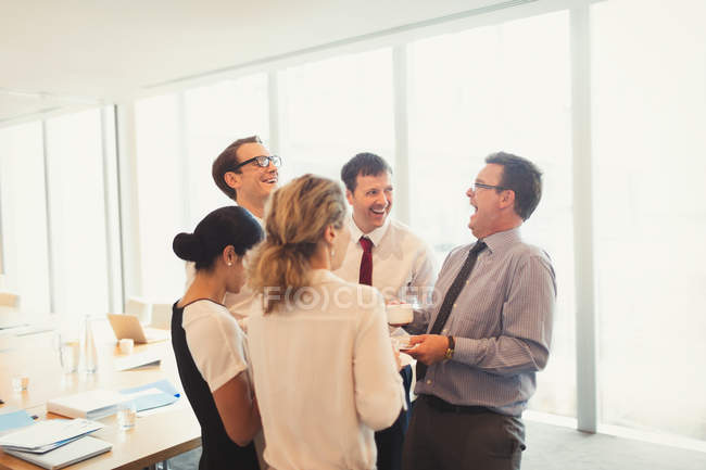 Laughing business people enjoying coffee break in conference room — Stock Photo
