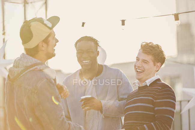 Young men laughing at rooftop party — Stockfoto