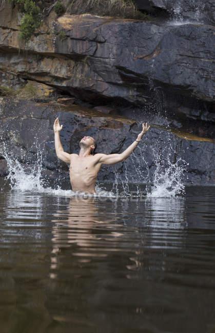Homme éclaboussant dans la piscine contre la roche — Photo de stock