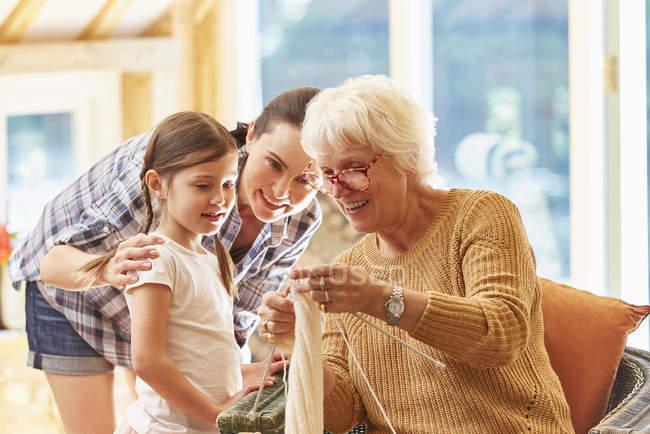 Grandmother teaching granddaughter knitting — Stock Photo