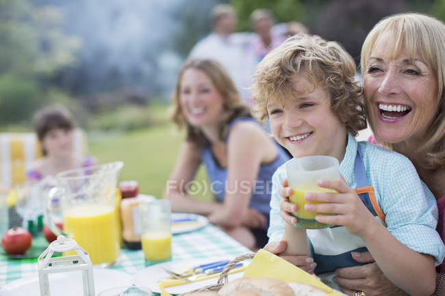 Happy family eating together outdoors — Stock Photo