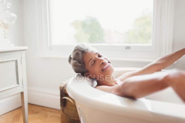 Sonriente mujer madura con los ojos cerrados disfrutando del baño - foto de stock