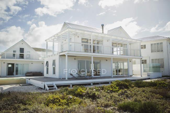 Белый пляжный домик под облаками — стоковое фото