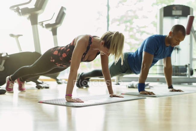 Man and woman doing planks at gym — Stock Photo