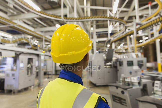 Worker in hard-hat watching printing press conveyor belts and machinery in printing plant — Stock Photo