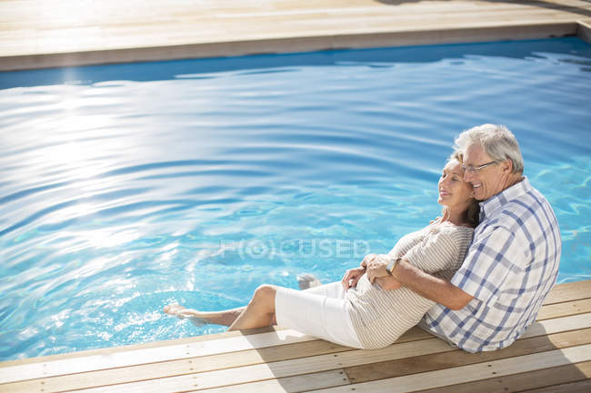 Senior couple relaxing by pool — Stock Photo