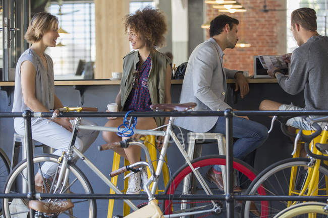 Friends hanging out talking and drinking coffee at cafe patio with bicycles — Stock Photo
