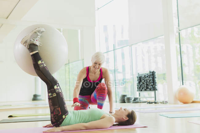 Personal trainer guiding woman with fitness ball between legs — Stock Photo