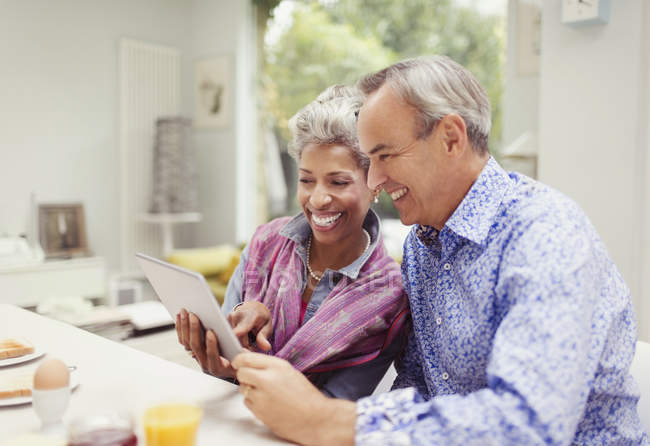 Smiling mature couple sharing digital tablet at breakfast table — Stock Photo
