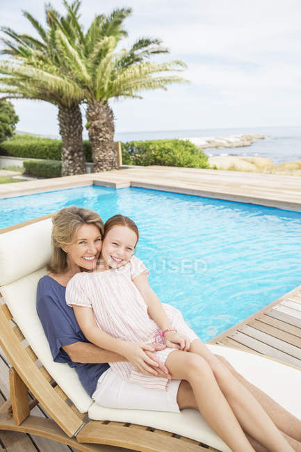 Grandmother and granddaughter relaxing at poolside — Stock Photo