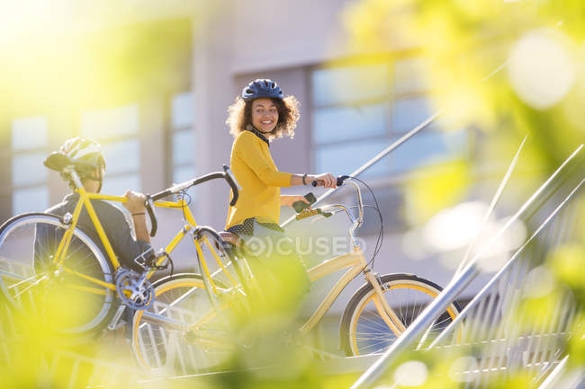 Smiling woman with bicycle in city — Stockfoto