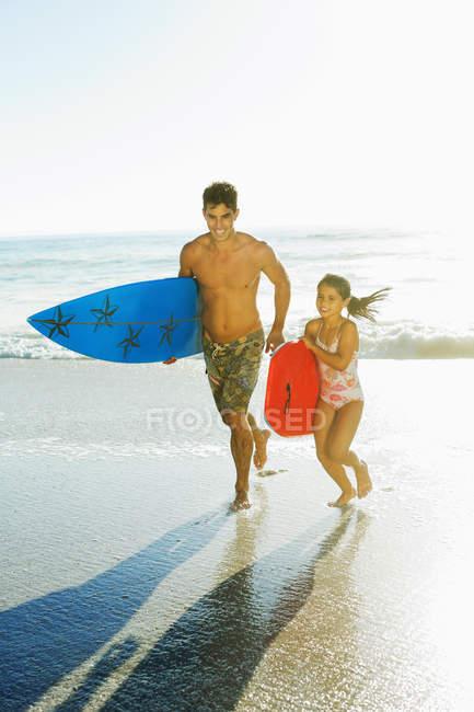 Pai e filha carregando prancha e bodyboard na praia — Fotografia de Stock