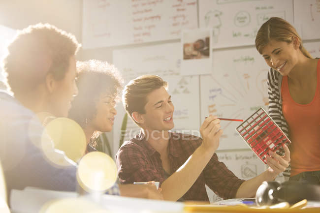 Business people looking at cube in meeting in modern office — Stock Photo
