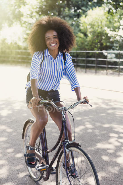 Portrait smiling woman with afro riding bicycle in park — Stock Photo
