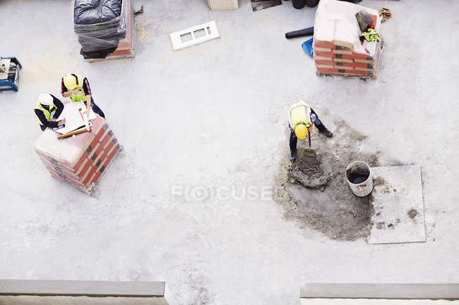 Overhead view of construction workers laying concrete at construction site — Stock Photo