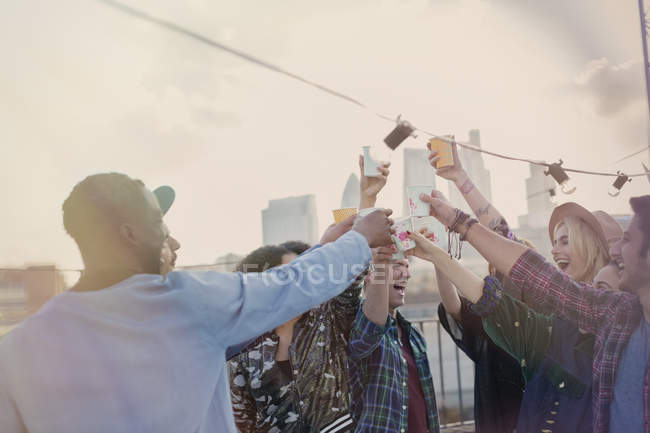 Enthusiastic young adult friends toasting cocktails at rooftop party — Stockfoto