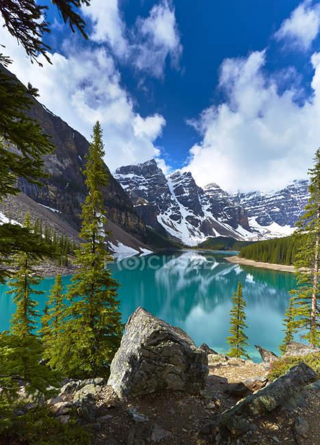 Снежные горы с видом на ледниковое озеро — стоковое фото