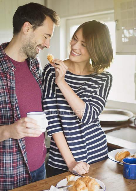 Novia de alimentación croissant de novio en la cocina - foto de stock