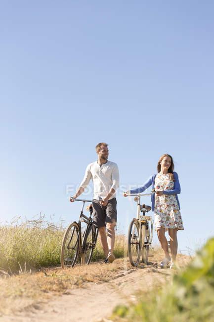 Молода пара ходіння велосипеди по грунтовій дорозі нижче Сонячний Синє небо — стокове фото