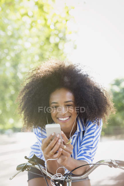 Smiling woman with afro listening to music with headphones and mp3 player on bicycle — Stock Photo