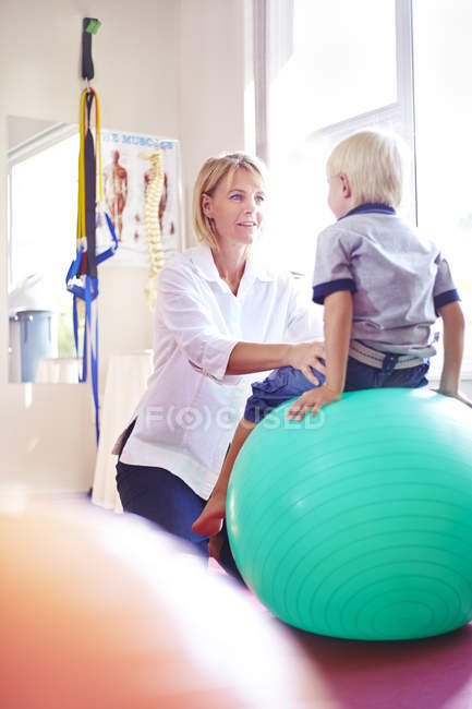Physical therapist holding boy on fitness ball — Stock Photo