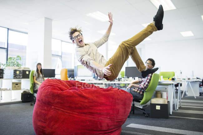 Empresario saltando en la silla beanbag en la oficina - foto de stock