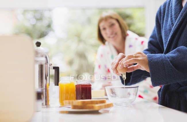 Woman watching husband crack egg in kitchen — Stockfoto
