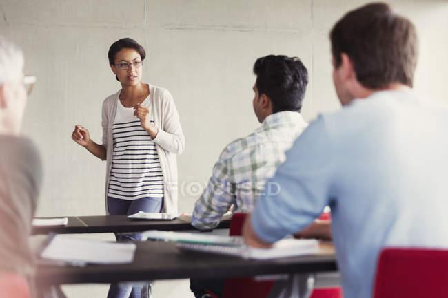 Professeur s'adressant aux élèves en salle de classe de l'éducation des adultes — Photo de stock