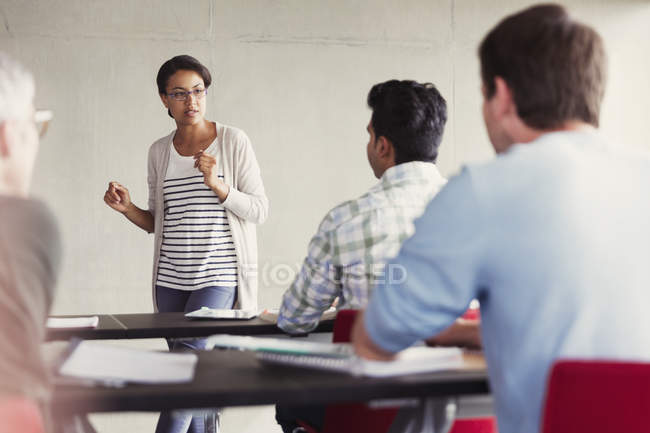 Profesor habla a los estudiantes en el aula de Educación de adultos - foto de stock
