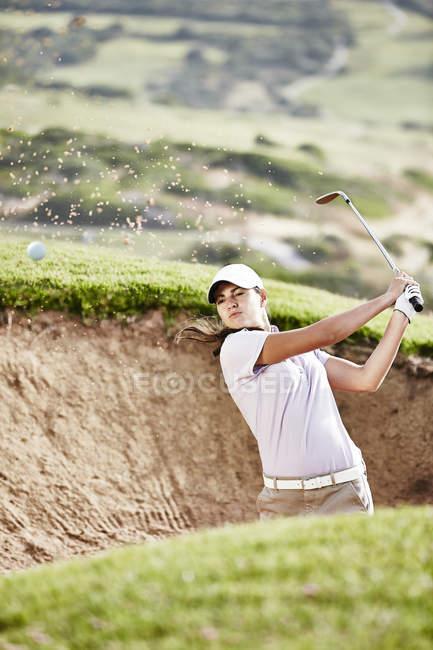 Femme oscillant entre la fosse de sable sur le terrain de golf — Photo de stock