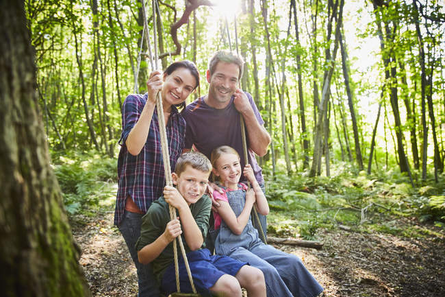 Portrait smiling family at rope swing in woods — Stock Photo