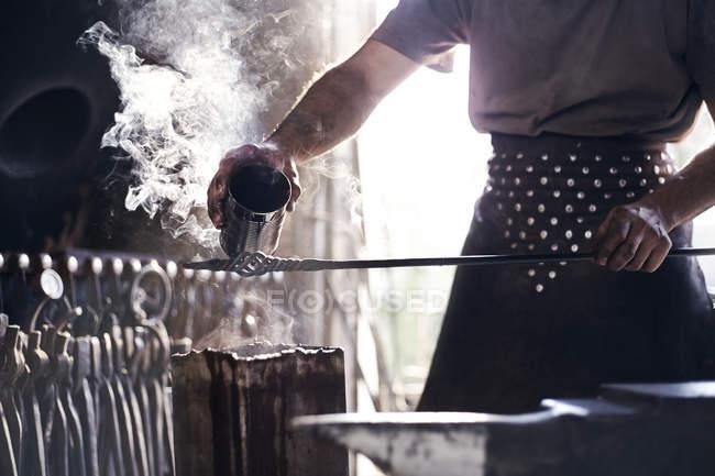 Кузнец, обливание горячей жидкости из кованого железа в forge — стоковое фото