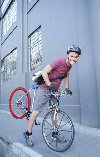 Portrait smiling bicycle messenger with helmet leaning forward on urban sidewalk — Stock Photo