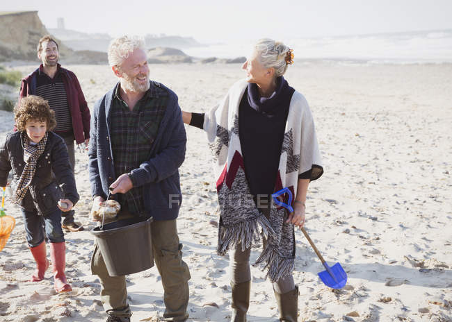 Multi-generation family clam digging on beach — Stock Photo