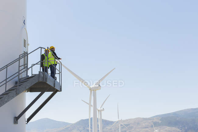 Workers standing on wind turbine in rural landscape — Stock Photo