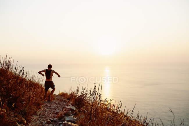 Coureur masculin avec sac à dos descendant sentier escarpé surplombant l'océan couchant le soleil — Photo de stock