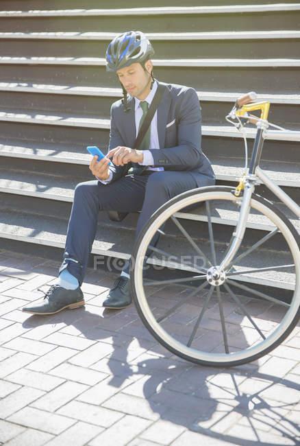 Uomo d'affari in tuta e casco sms con cellulare accanto alla bicicletta su soleggiate scale urbane — Foto stock