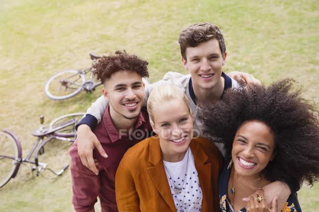Портрет улыбающихся друзей, обнимающихся в парке — стоковое фото