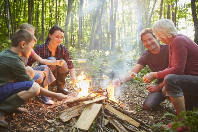 Mehrgenerationenfamilie grillt Marshmallows am Lagerfeuer im Wald — Stockfoto